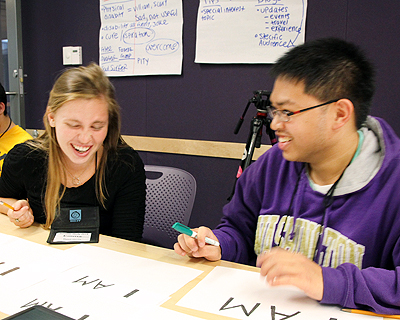 Image of students laughing while working