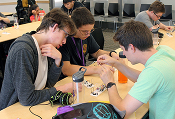 A mentor shows two students how to assemble circuitry for a keyboard.