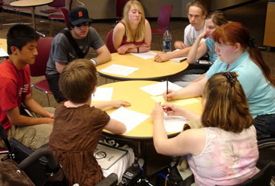 Photo of a large group of students collaborate on a team project at a table
