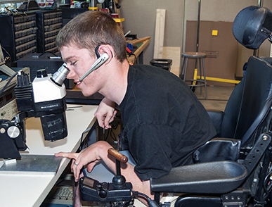 A student in a wheelchair looks into a microscope.