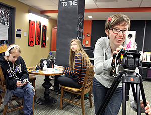 Image of students doing a filming activity in a student lounge