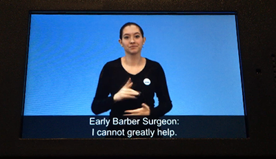 Video still of an audio tour that has a sign language interpreter as well as closed captions.
