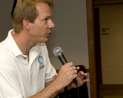 Image of faculty member Scott holding a microphone giving a speech.