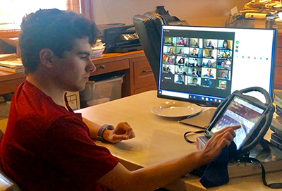 A student uses an alternative communication device while in an online class.