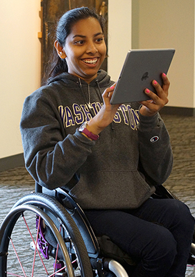 A student in a wheelchair looks at an accessible document on an iPad.