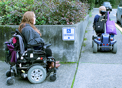 Two students in power wheelchairs make use of accessible ramps on the University of Washington campus.
