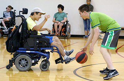Two students with disabilities play basketball.