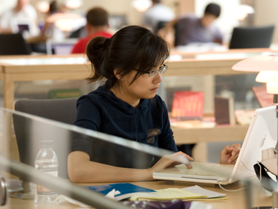 Image of a student working on a laptop in a library
