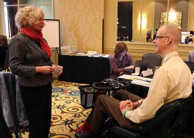 Photo of DO-IT Director Sheryl Burgstahler talks with AccessSTEM CBI Participant Christopher Andersen in the lecture room at the Hotel Deca in Seattle.