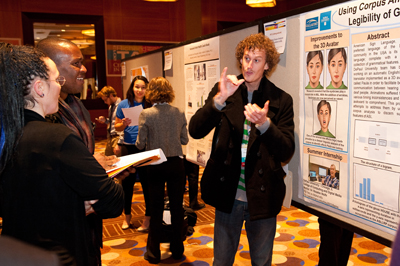 Photo of AccessComputing participant Larwan explains his poster and research at the Tapia Conference.