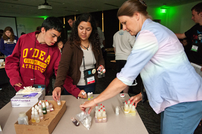 Photo of DO-IT Staff member works with scholars to do a science experiment.