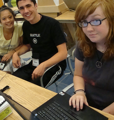Photo of several students posing for the camera while working on laptops