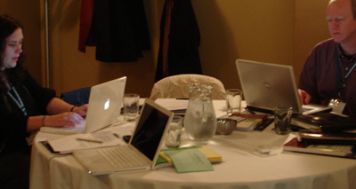 Photo of particpants at a round table full of laptops