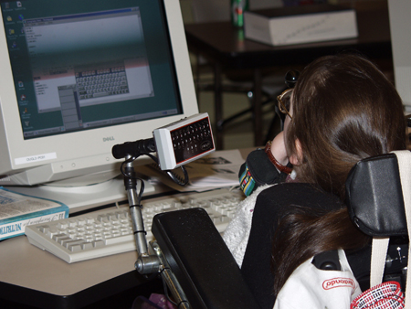 Photo of a female student in a wheelchair operating a computer