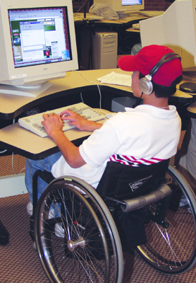 Photo of student in a wheelchair working at a computer workstation