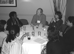 Photo of CBI participants talking at a round table while enjoying something to drink