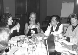 Photo of discussion between participants at a round table is aided by a sign language interpreter and laptop computer