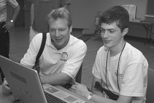 Photo of DO-IT Staff member Scott Bellman looking at a laptop computer screen with a DO-IT Scholar in classroom.