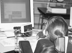Image of Scholar in a wheelchair uses assistive technology to control her computer mouse using her chin.