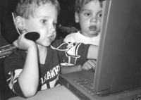 Photo of young children working on a laptop in the computer lab