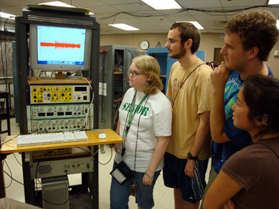 Photo of group of students watching with interest as they gather around a rack of scientific equipment