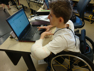 Photo of male student in wheelchair works at a laptop