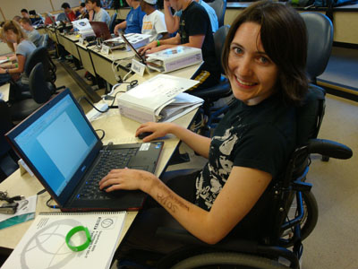 Photo of female student smiling while working on a laptop