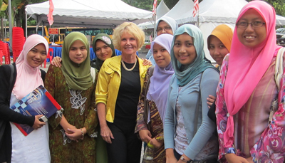 Photo of DO-IT director Sheryl Burgstahler poses for a photo with female students from the University of Malaysia.
