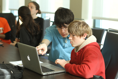 Student working with mentor on laptop.