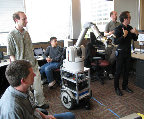 Picture of students and staff around a robotic arm.