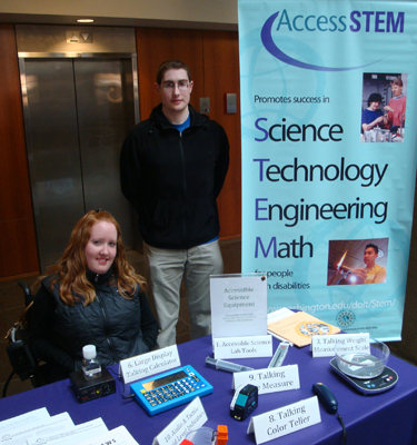Picture of two DO-IT staff members at an AccessSTEM display showing different equipment for making a science lab accessible