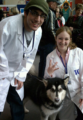 Group photo of DO-IT staff Noah Seidel and Jennifer Gears pose with the UW mascot, Dubs, at Paws on Science.