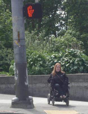 Photo of DO-IT Ambassador Kayla waits to crosswalk near the UW campus