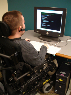 A male student in a wheelchair works with a computer.