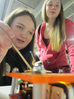 Photo of two female students use electrodes to conduct an experiment.