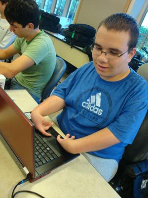 Photo of 2012 Scholar Garrett wearing a blue shirt types on a laptop.