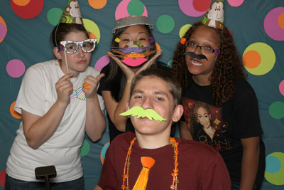 Photo of 2012 Scholars Alicia, Grace, and Aaliyah pose with 2010 Intern Benjy wearing decorated paper glasses and mustaches in front of a polka-dot backdrop.