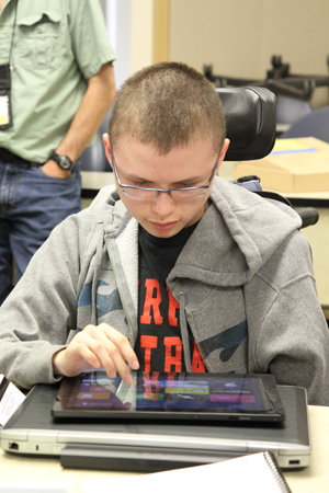 Photo of DO-IT Scholar Colton exploring tablet technology at Microsoft.