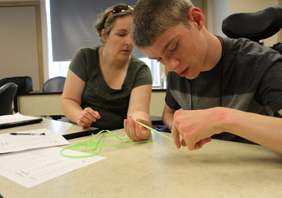 Photo of DO-IT Scholar Cody working on a class project on the UW campus.