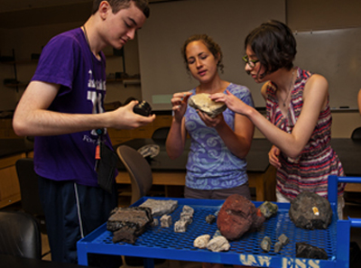 Photo of Phase II DO-IT Scholars Peter and Lindsay look at geological rocks with an instructor