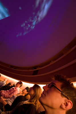 Photo of people sitting around the edge of the University of Washington planetarium looking up at the night sky on a giant screen
