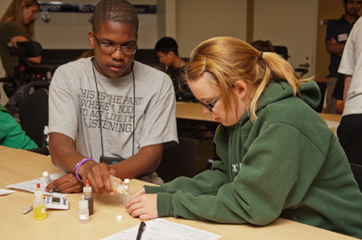 Photo of Phase I DO-IT Scholars Julian and Karly holding different bottles of chemicals and work together in a classroom.