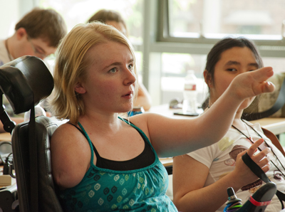 Photo of Phase I DO-IT Scholar Kayla holds up her arm and speaks up in a classroom, with Phase I Scholar Clarissa sitting next to her