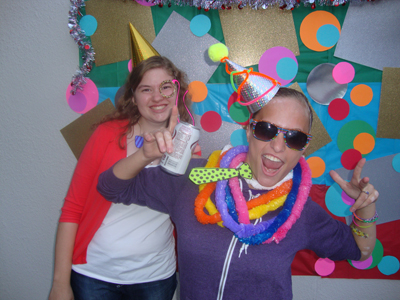 Photo of DO-IT Interns Erika and Kaylie are dressed up in party hats and crafts while posing in front of a polka dot background