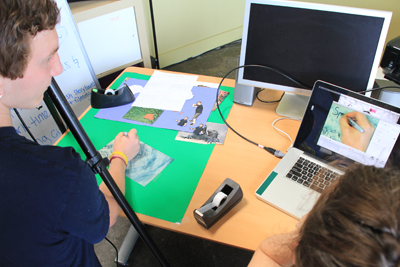 Photo of Phase II DO-IT Scholar Eric is drawing on a piece of paper under a camera, which is also shown on the laptop next to him.