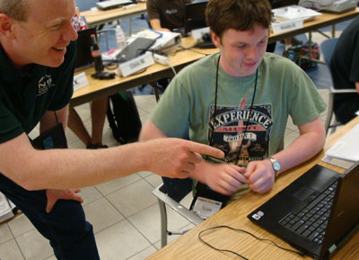 A mentor works with a high school student in a computer lab.