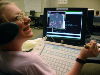 A high school student uses assistive technology with her laptop.