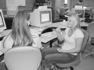 Photo of Two DO-IT Ambassadors using sign language to talk to each other in a computer lab.