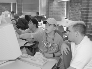 Photo of DO-IT Scholars receive computer assistance from DO-IT Ambassadors.