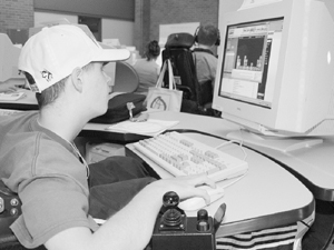 Photo of Student in wheelchair using a mouse to work on a computer program about blocks.